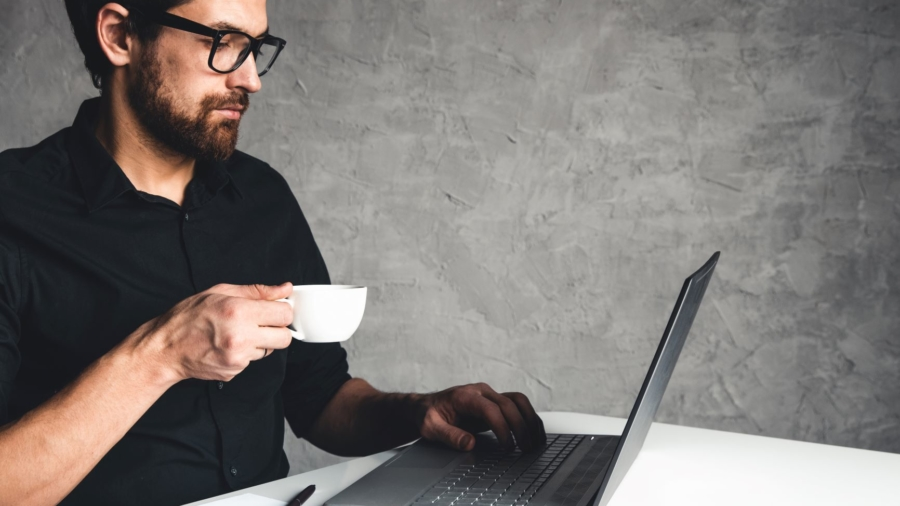 a-man-sits-with-a-laptop-in-a-black-shirt-business-LAUMGKE2