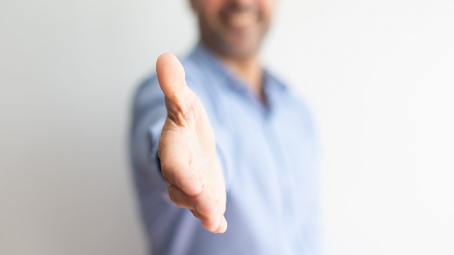 Closeup of business man offering hand for handshake. Entrepreneur greeting you. Deal concept. Cropped front view.