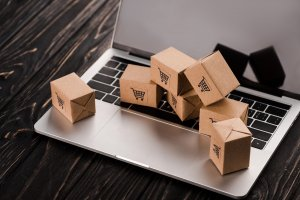 small carton boxes on laptop with blank screen, e-commerce concept