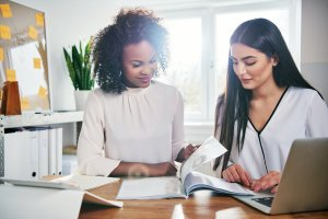 Two young businesswomen working on a report