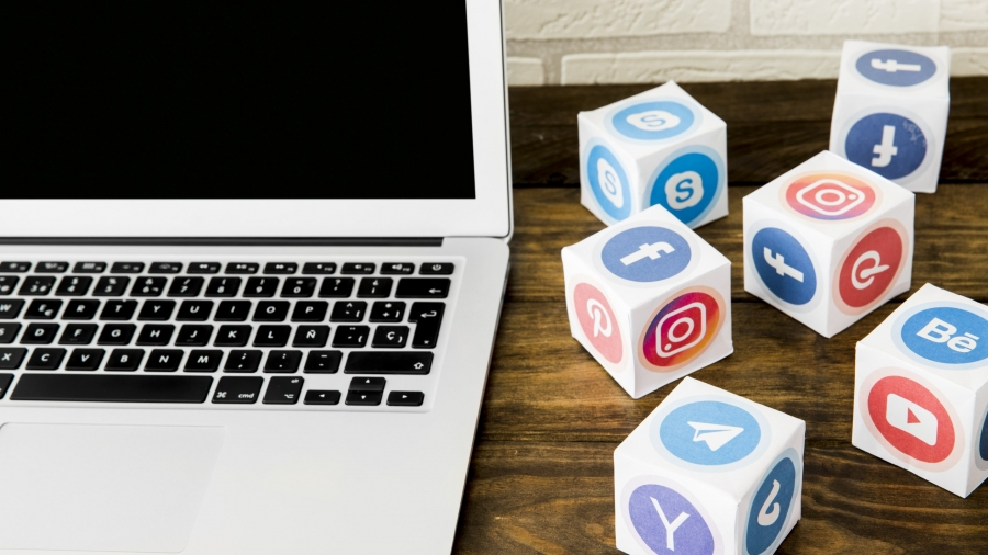 laptop-near-boxes-of-social-application-icons-on-table
